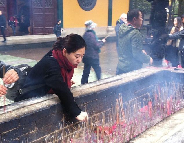 Una mujer deposita ofrendas en un templo chino. (Foto José Luis Barceló © Copyright 2018)