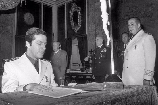 Adolfo Suárez jura arrodillado su cargo como nuevo vicesecretario general del Movimiento, en un acto celebrado el 23 de abril de 1975 en el Palacio de El Pardo, presidido por Francisco Franco.  Asistieron, el ministro secretario general del Movimiento, Fernando Herrero Tejedor (d), y Fernando Fuentes de Villavicencio (3º d).