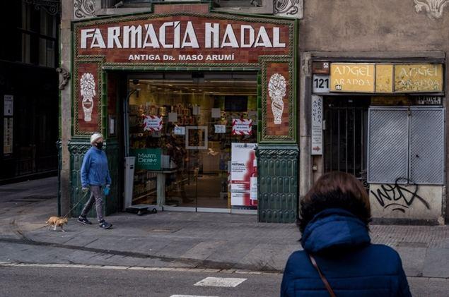 Una mujer porta una mascarilla mientras pasea a su perro frente a una farmacia en el centro de Barcelona, España, el 18 de marzo de 2020. (Xinhua/Joan Gosa).